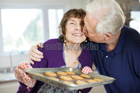 senior couple kissing with home baked