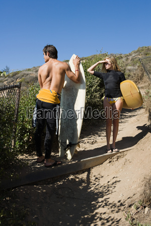 young couple with surfboards