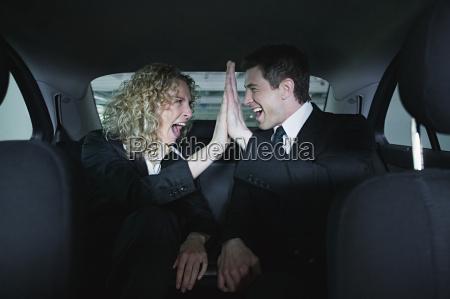 colleagues in car doing a hi