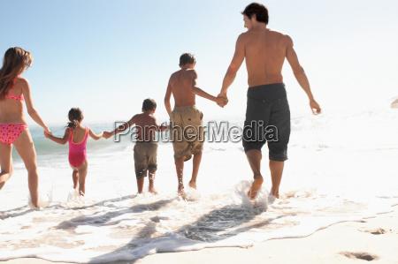 family walking into the sea