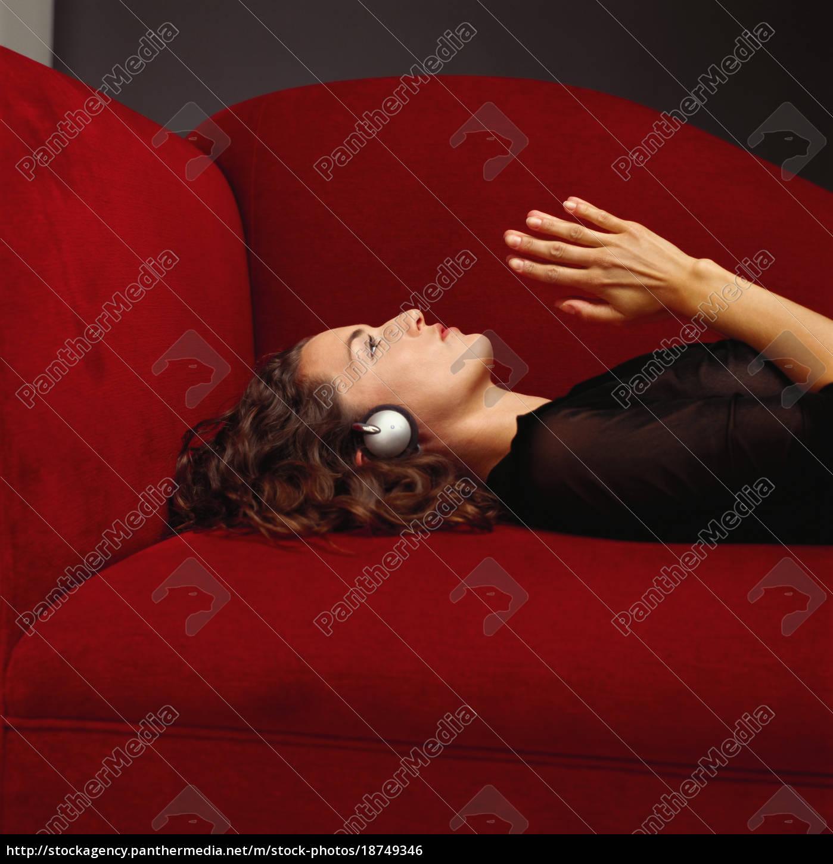frau, trägt, kopfhörer, auf, dem, sofa - 18749346