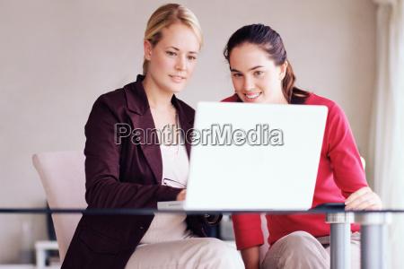 two women using laptop computer