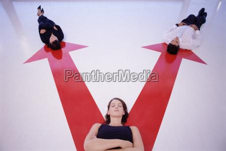 three people lying on arrow signs