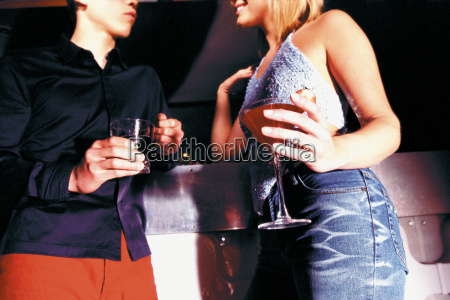 man and woman holding drinks in