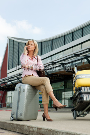 mid adult woman sitting on luggage