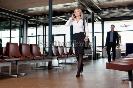 businesswoman using phone in airport