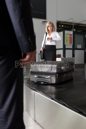 mid adult businesswoman waiting for luggage