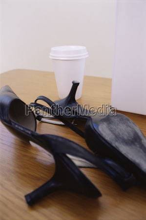high heeled shoes and cup on
