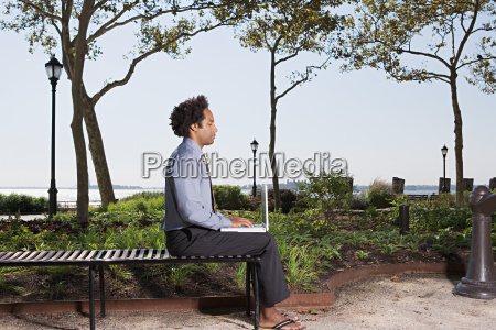 man telecommuting in einem park