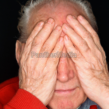 senior man covering his eyes with