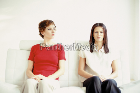 two women sitting on a sofa