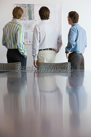 businessmen looking at architectural plans