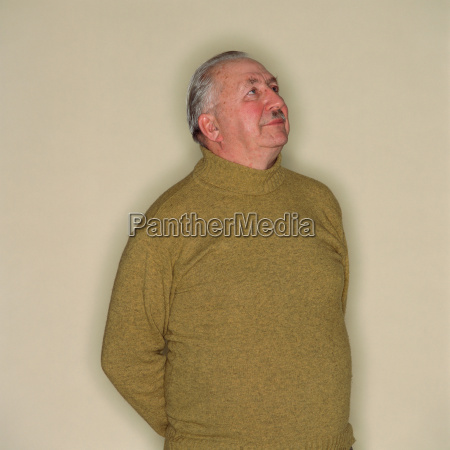senior man with hands behind back