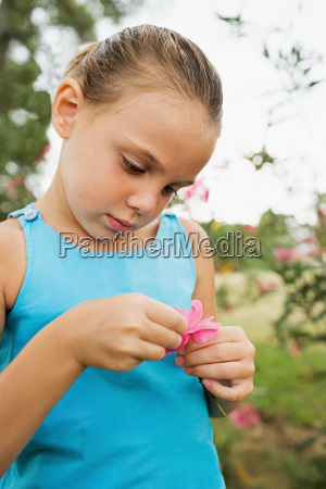 girl pulling petals from flower