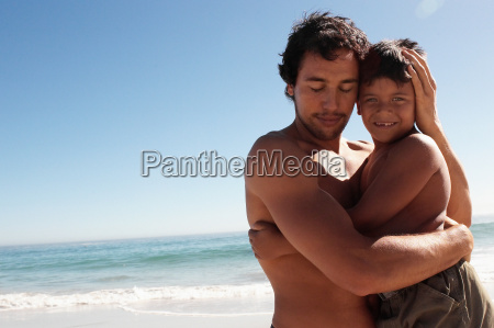 father hugging son on a beach