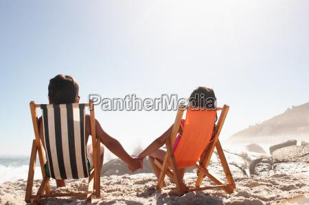 children holding hands on a beach