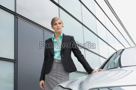 businesswoman standing by car