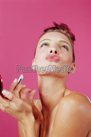 woman putting on lipstick