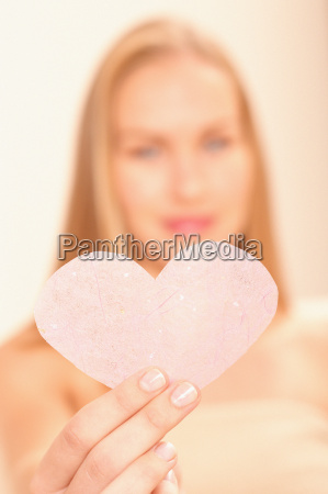 woman holding pink heart