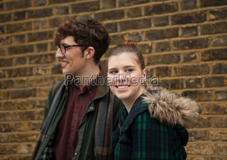 young couple by brick wall smiling