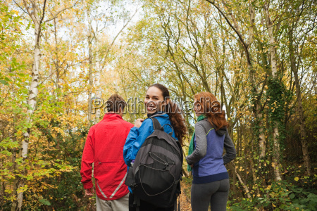 young friends walking into forest