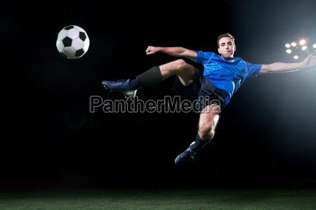 junger fussballspieler der in luft springt
