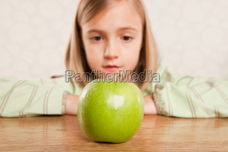 little girl looking at an apple