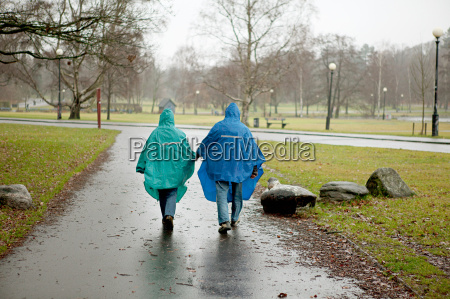 senior couple in waterproof clothing walking