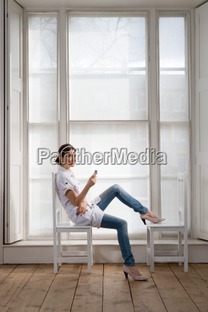 woman sitting on chair with cell