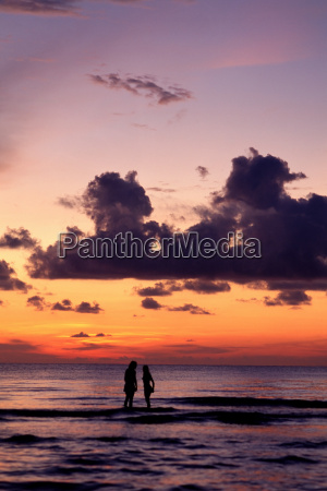 couple in sea at sunset
