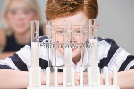 boy looking at test tubes