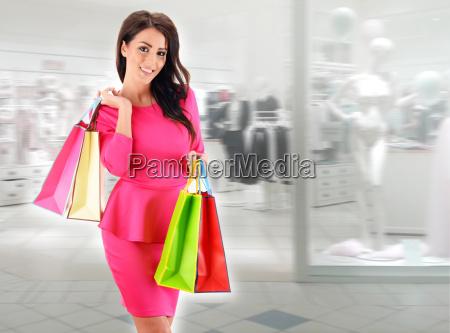 junge frau mit taschen in einkaufszentrum