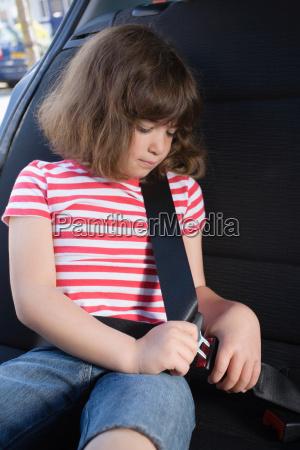 girl fastening her seatbelt