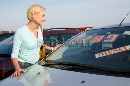 a woman looking at a car