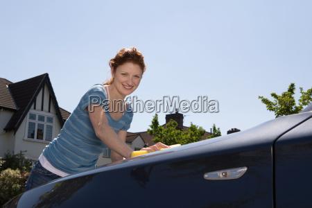 a woman washing a car