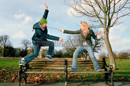 couple playing on park bench