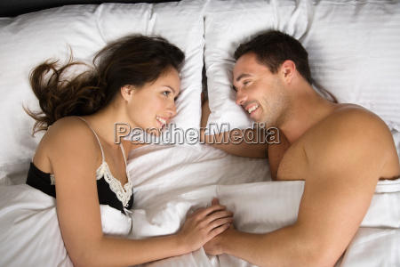 a couple lying in bed face