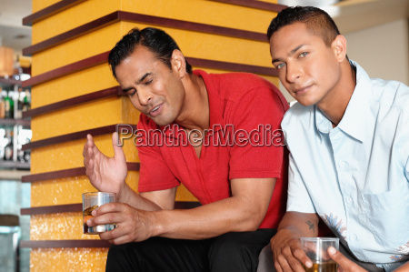 two men sitting in bar