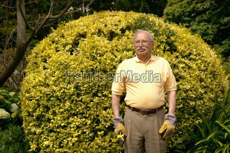 senior man standing in a garden