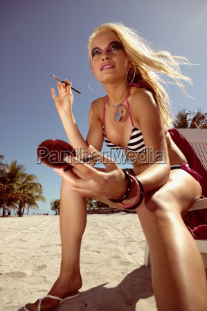 woman applying make up on beach