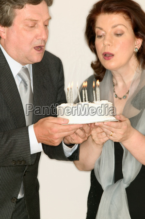 mature couple blowing out candles on