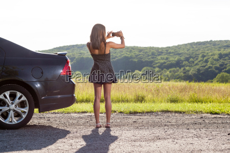 young woman photographing rural scene with