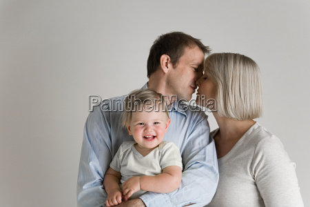 kissing couple with baby