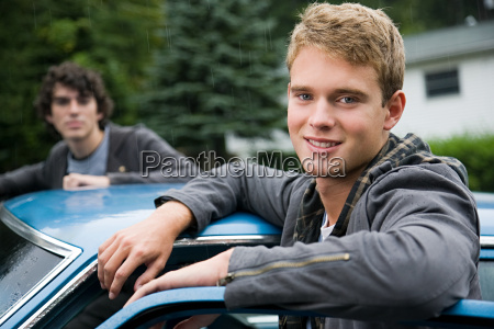 two young men by car