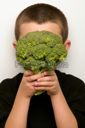 boy covering face with broccoli
