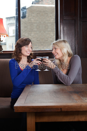 two young women in bar toasting