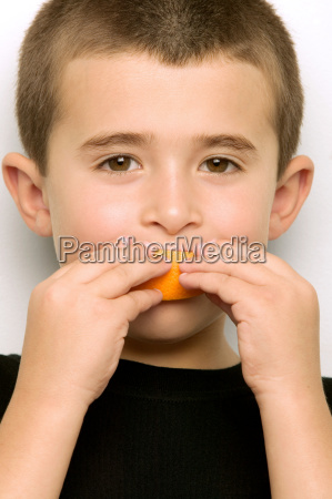 boy eating an orange segment