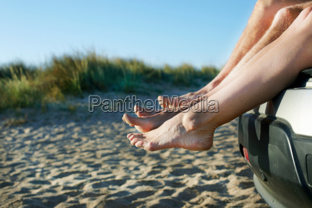 mid adult couple sitting barefoot on