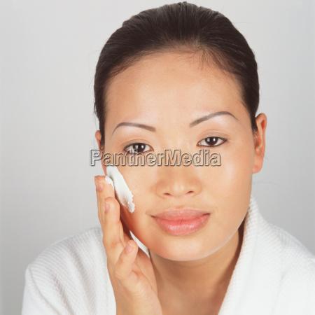 woman applying moisturiser to cheek