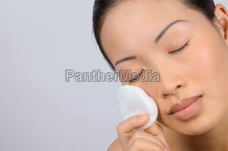 woman applying make up with cotton